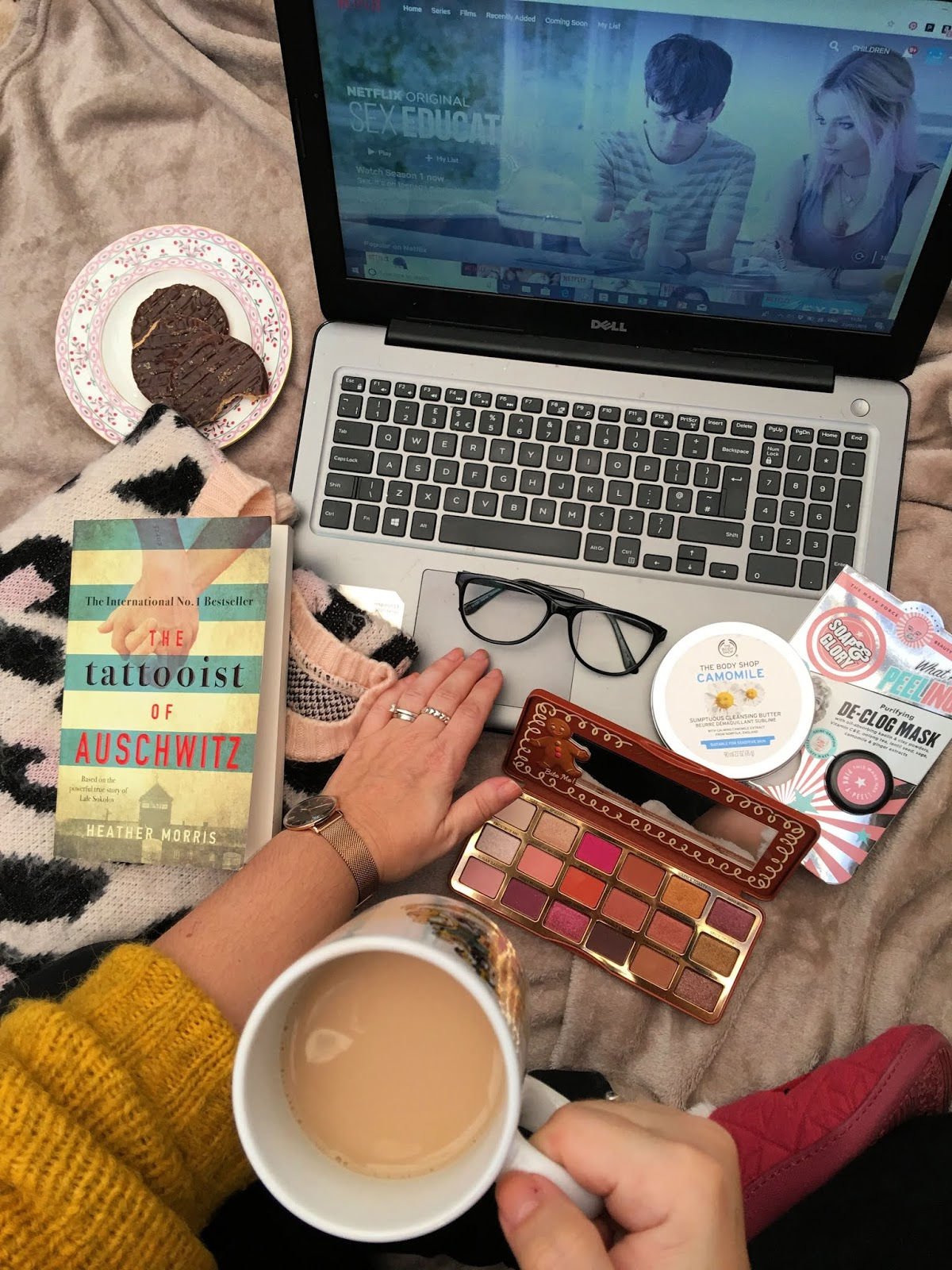 Flatlay of tea, makeup and netflix