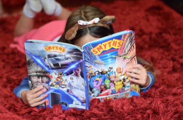 Child reading Smyths Toys Superstores catalogue