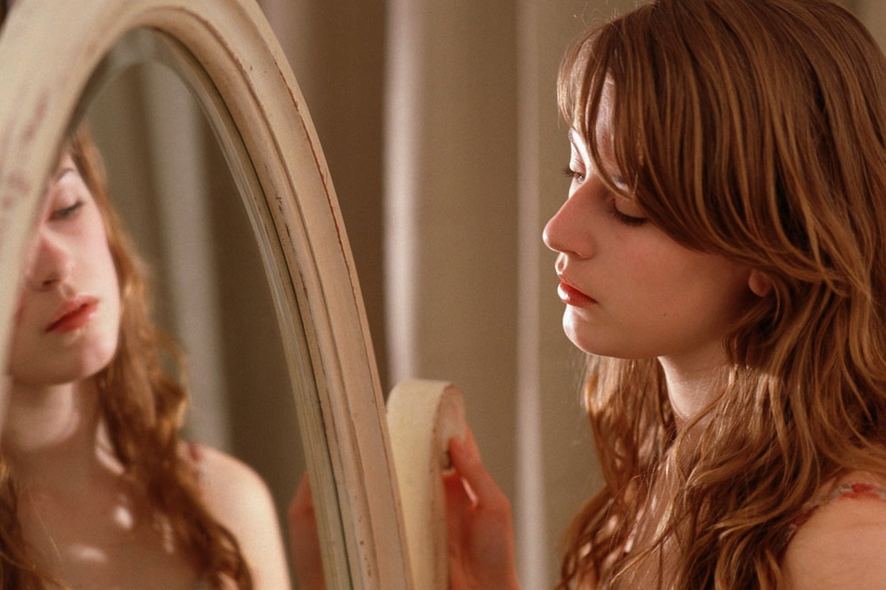 Mulher se olhando no espelho pensativa
