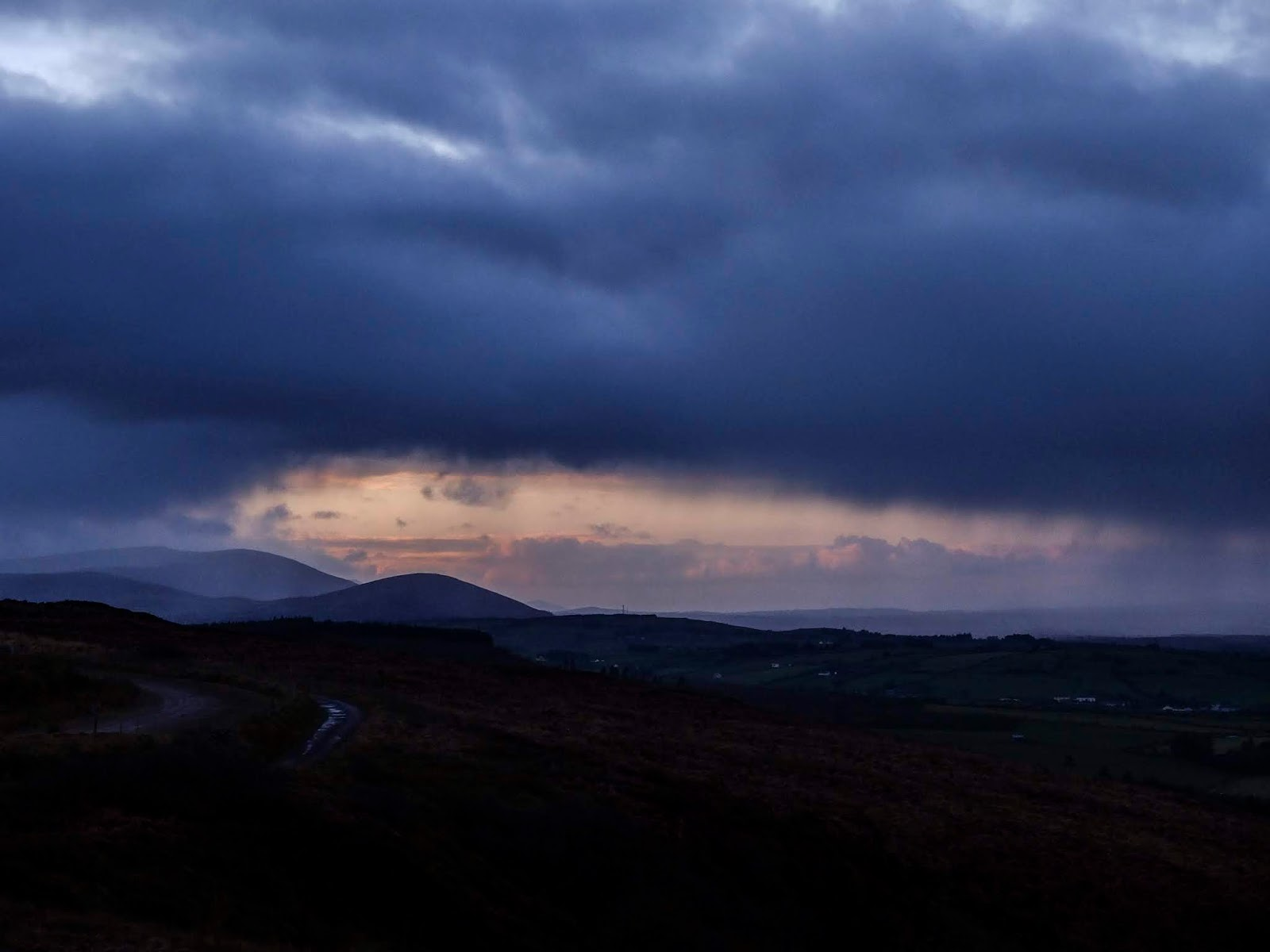 Rain clouds in a valley in the Boggeragh Mountains with sunset clouds in the distance.