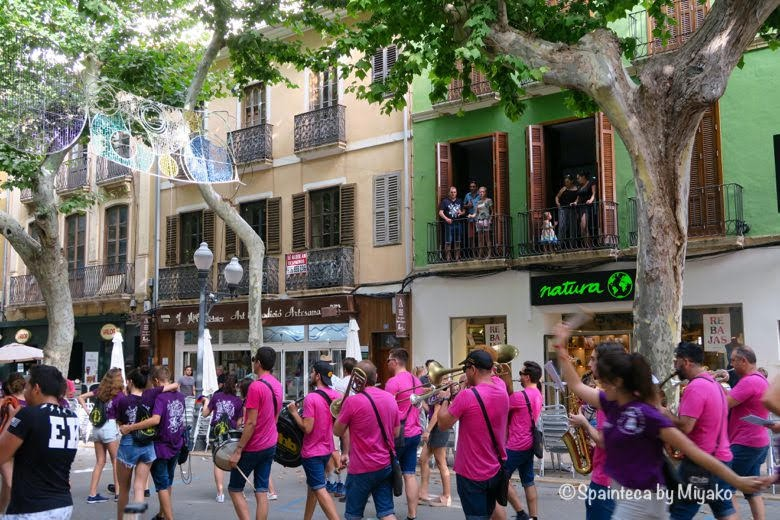 スペインのデニアの中央通りで楽器を演奏しながら行進する若者たち