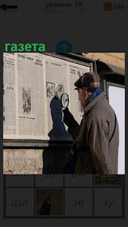 Мужчина в кепке читает газету на стене используя лупу