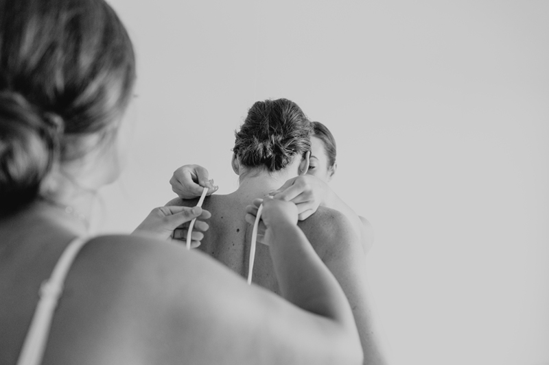 bw shot of bride getting dressed
