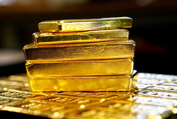 Gold slips but is on track for small gains for the week on a softer dollar
