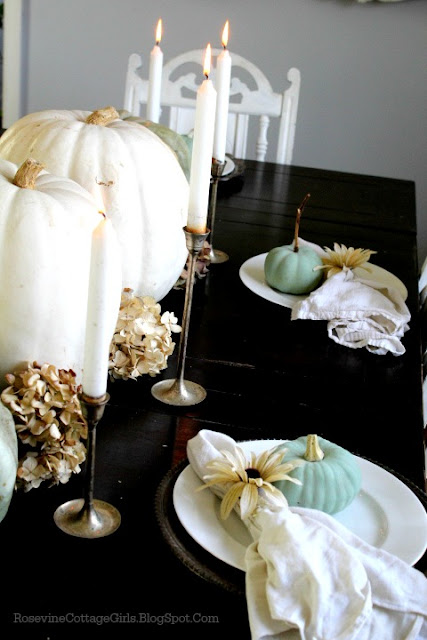 Farmhouse Thanksgiving Tablescape - Rosevinecottagegirls.com | black table with pumpkins and dried flowers, silver candlesticks, White plates and small green pumpkins with cloth napkins