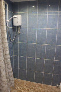 Picture of shower in wet room, with curtain and tiled floor.