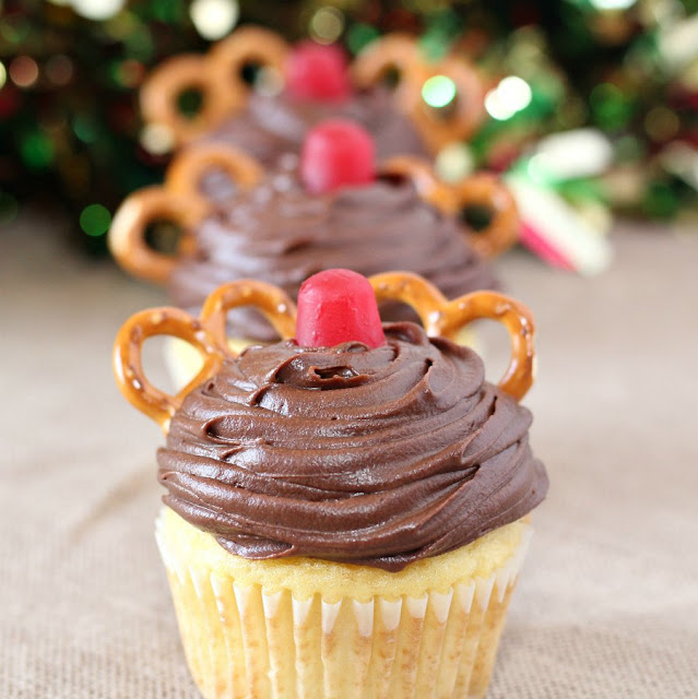 close up of a row of cupcakes decorated with chocolate frosting, a red gumdrop and pretzels to look like Rudolph