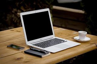 laptop, cafe y celular sobre mesa