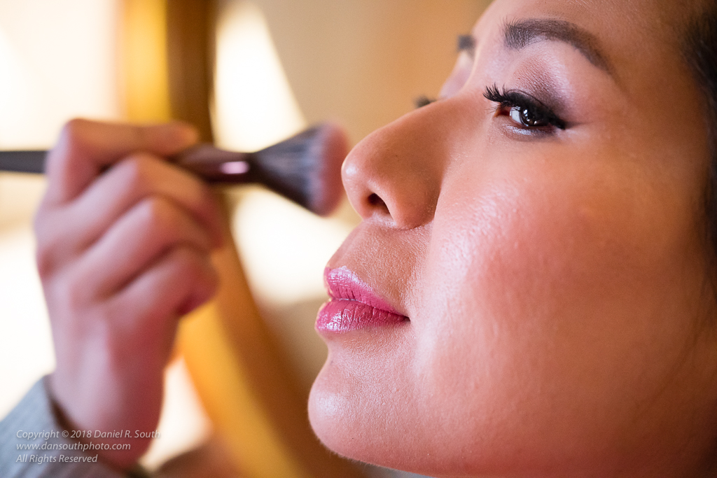 a photo of a makeup artist working with a bride before a wedding