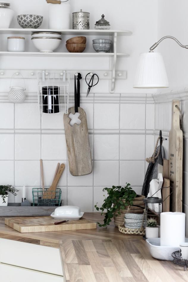 Blick auf die Küchenarbeitsplatte mit Holzfarbenen, weißen und schwarzen Küchenaccessoires