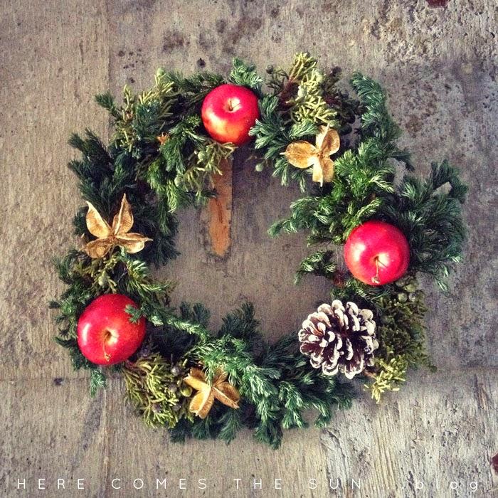 コンクリート壁に姫リンゴと樅の木の実の手作りのクリスマスリース
