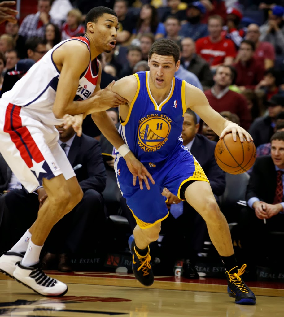 Golden State Warriors guard Klay Thompson (11) gets past Washington Wizards forward Otto Porter Jr. (22) in the first half of an NBA basketball game on Sunday, Jan. 5, 2014, in Washington. (AP Photo/Alex Brandon)