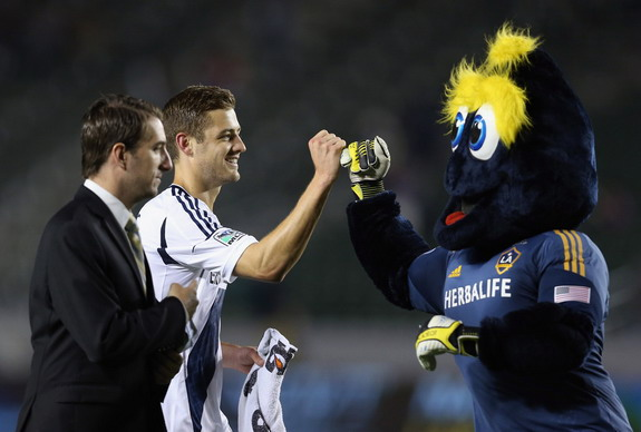 Los Angeles Galaxy player Robbie Rogers is congratulated by the club's mascot Cozmo