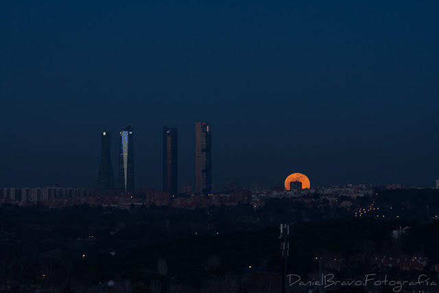 Luna llena saliendo detrás de los edificios al anochecer.