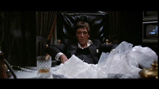 Fotograma de El precio del Poder. Toni Montana frente a montones de bolsas de polvos de talco.