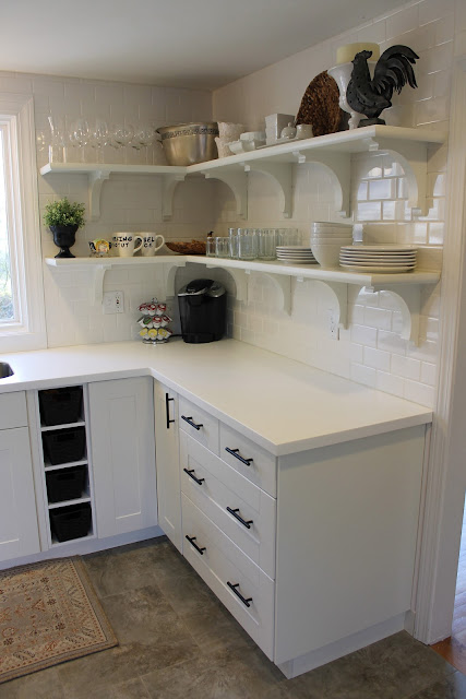 An all white cabinet and countertop with black handle pulls and plates on shelves in kitchen.