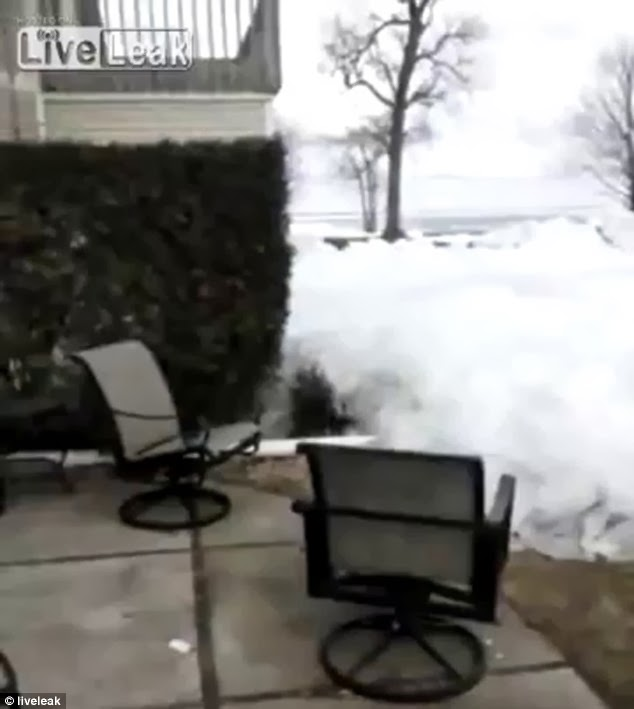 Taking over: The 'ice tsunami' creeps towards garden furniture which is hastily moved by the homeowner who filmed these bizarre scenes