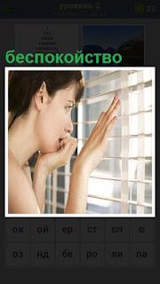 около окна стоит женщина с беспокойством смотрит на улицу