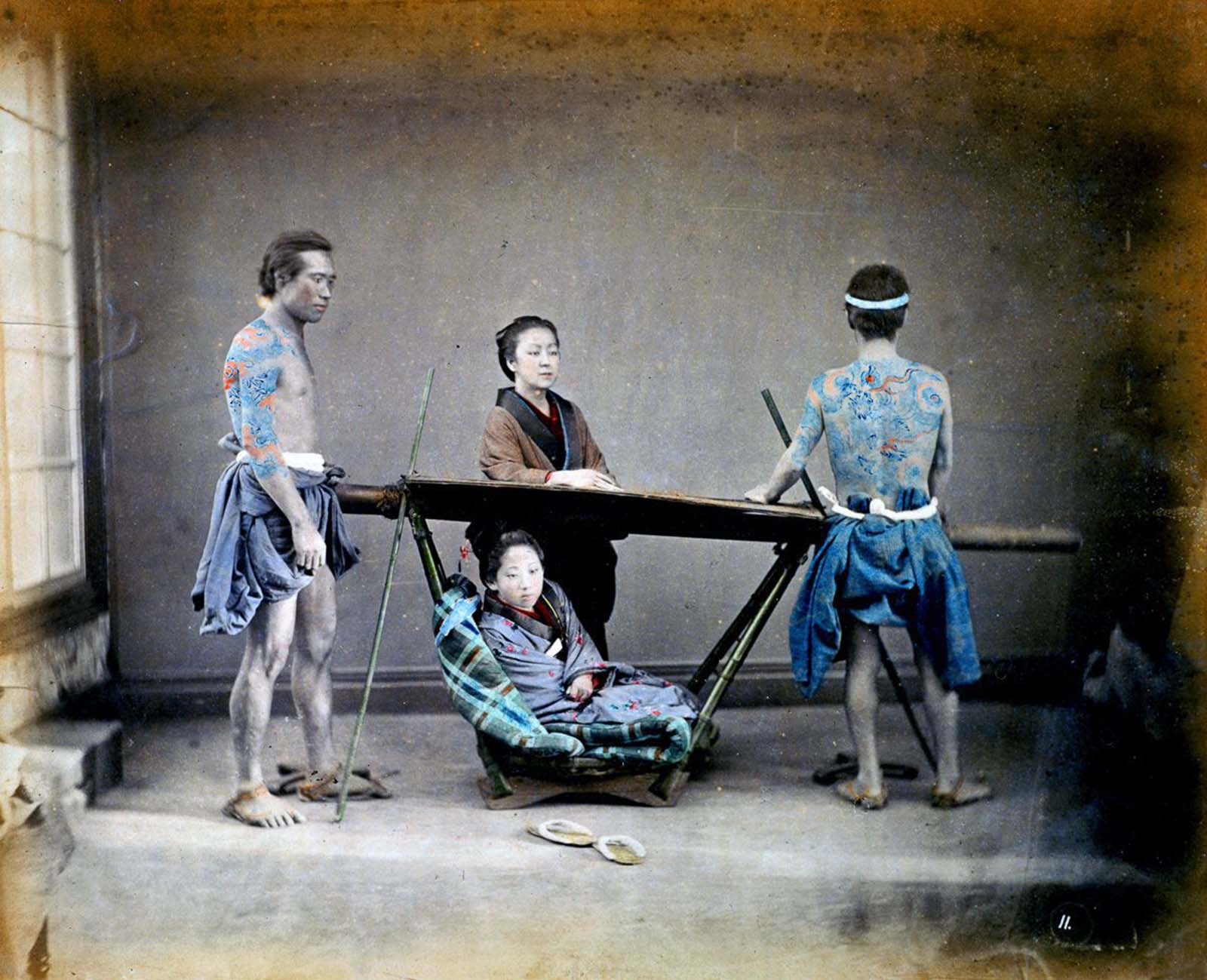Two tattooed kago bearers prepare to lift a woman in a kago, or sedan chair. 1865.