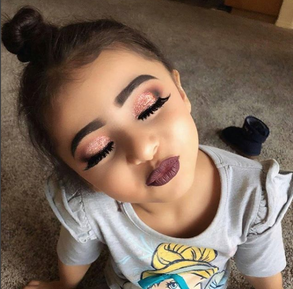 Checkout this little girl with a face full of heavy makeup