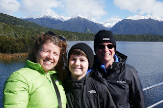 Two white women and their 10 year old son pose for a photo on the deck of a boat, with white-capped mountains behind