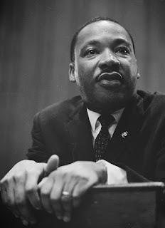 A black and white photo of Martin Luther King, Jr gripping a lectern with both hands and leaning toward them and toward the viewer. His gaze is up and to the left, and his lips are slightly pursed as though he is about to speak.