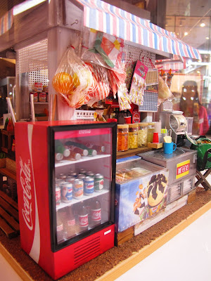Corner of a modern dolls' house miniature Hong Kong Joyful Store, showing a drink fridge and an ice cream freezer.