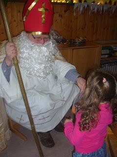 Nikolaus verteilt Geschenke an eins der Kinder