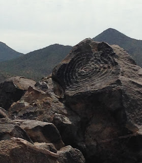 Pile of rocks against a mountain backdrop. One rock juts up with a large spiral petroglyph carved into its surface.