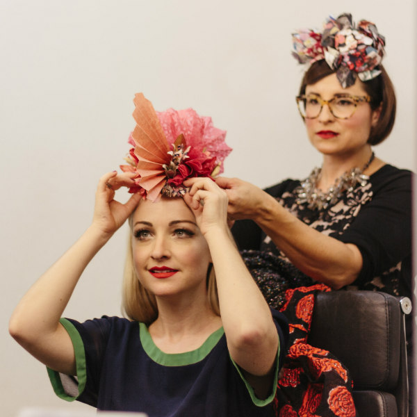 fitting an origami floral fascinator to the top of Kate Miller-Heidke's head
