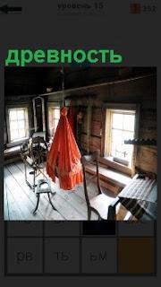 В помещении древность, старинные люлька, стулья и стол, низкие окна