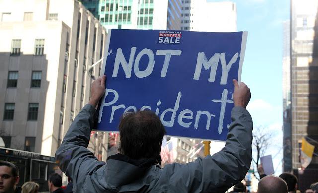 """Donald Trump """"no es mi presidente""""  hombre agarrando un cartelon en sus manos"""