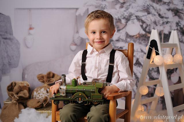 mały chłopiec na sesji studyjnej świątecznej ze śniegiem i kolejką uśmiechnięty