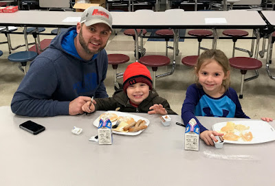 A man and two children sitting at a table in a cafeteria enjoying their breakfast and milk