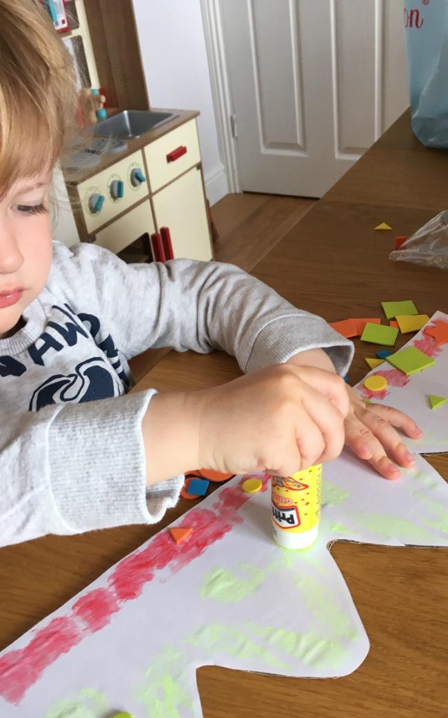 toddler using Pritt glitter stick on crown