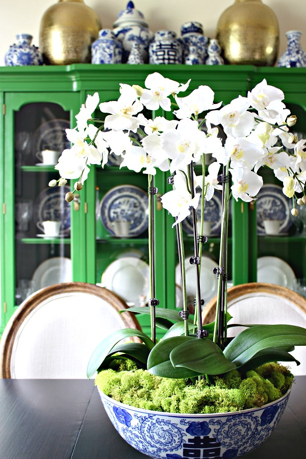green china cabinet, blue and white accessories, dining room, orchid arrangement
