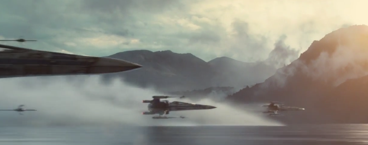 A group of X-wing fighters fly over a misty lake with snow covered mountains in the background