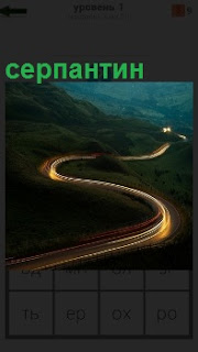 В темное время суток светится извилистая дорога серпантин между гор уходит дальше