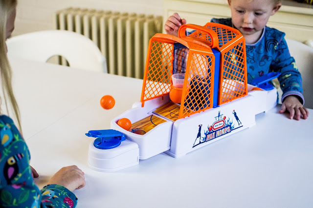 Game play of the Little Tikes Hot Hoops game with a ball in the air heading towards the hoop