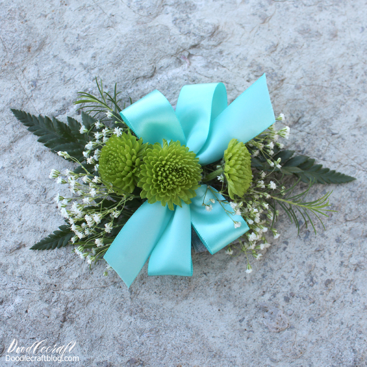 Fresh flowers and satin ribbon in aqua made into a wrist bouquet.
