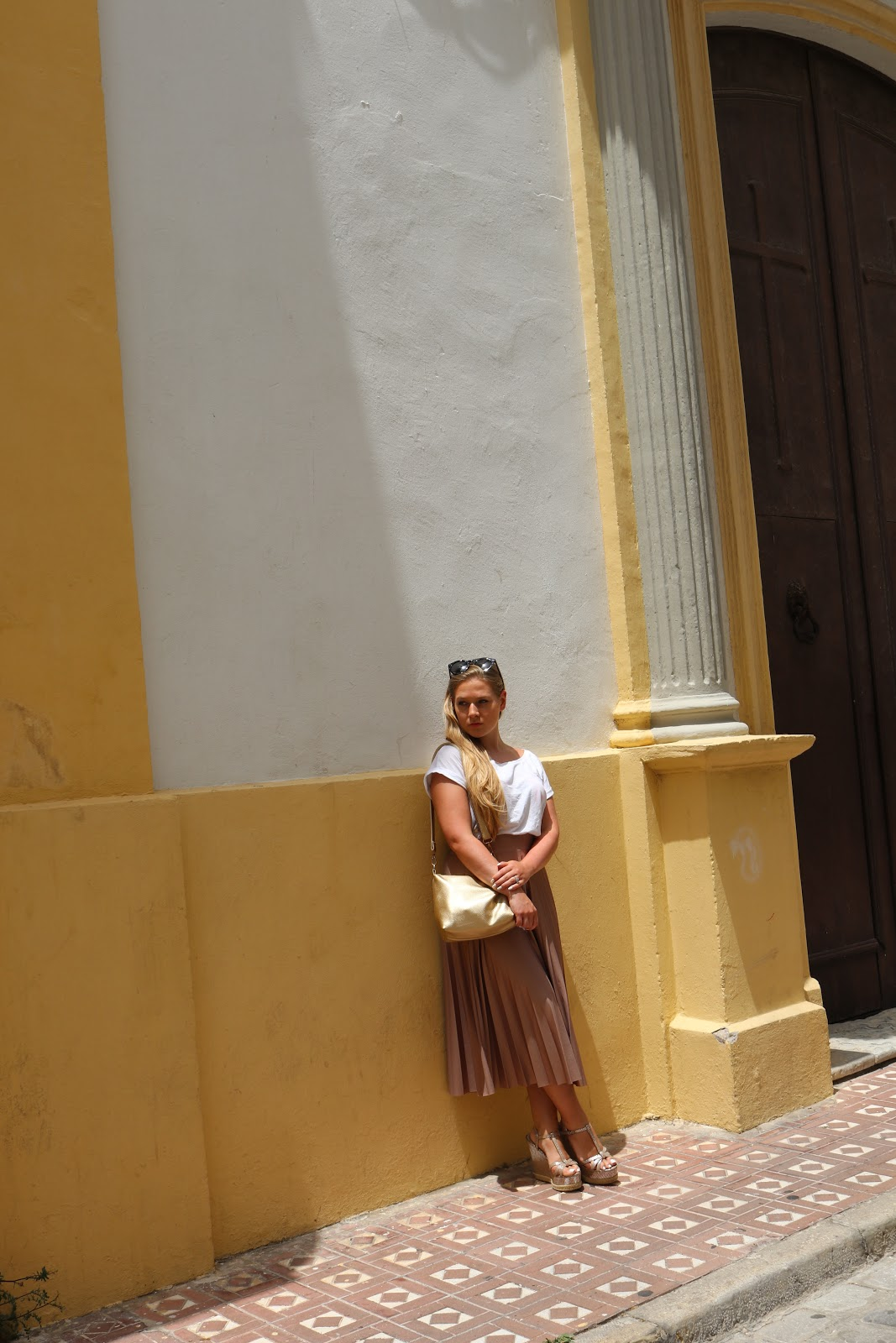 Blonde girl wearing metallic skirt against yellow walls in Tarifa, Spain