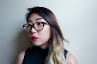 Photo of Franny Choi. Franny has long hair that is dark brown at the top and becomes lighter, eventually blonde at the bottom. She stand against a white backdrop, looking off into the distance. She wears glasses and a black tank top, and has bright red lipstick.