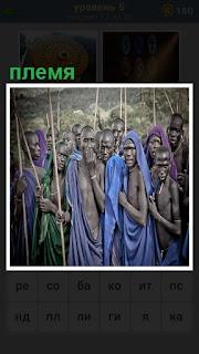 Стоит племя, несколько человек с копьями и в традиционной одежде