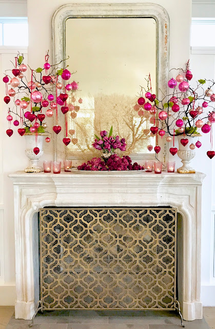 Valentine's Day Mantle Decor; heart ornaments, red ornaments, pink antique ornaments, pink tulips, pink flowers, antique mirror, limestone mantle