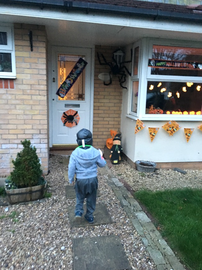 toddler-walking-up-to-house-decorated-for-halloween