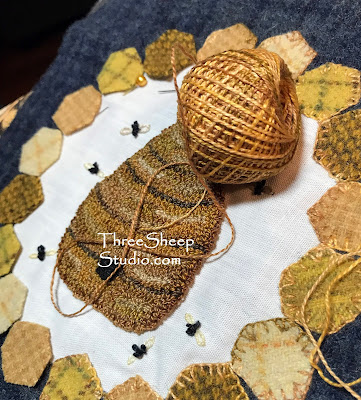 A Bee Skep surrounded by golden yellow honeycomb and a smattering of bees - 'The Hive' punch needle and wool applique pattern by Rose Clay at ThreeSheepStudio.com
