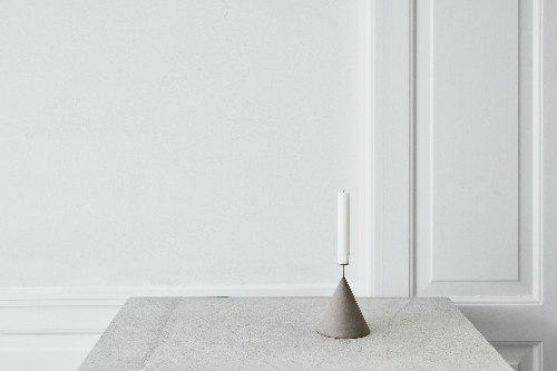 Leuchtend Grau: Ein schlichter Kerzenständer aus hellem Stein steht auf einem Tisch.