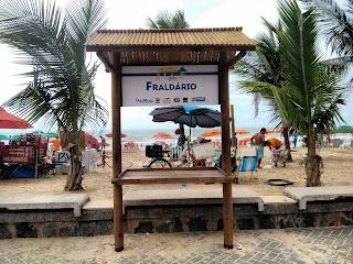 """Fotografia colorida de uma estrutura de madeira com um pequeno telhado e uma bancada no calçadão da praia de Boa Viagem, no Recife, com a identificação """"Fraldário"""". Por trás, guardas-sois, cadeiras, bicicletas e  pessoas na areia, o mar e o céu azul."""