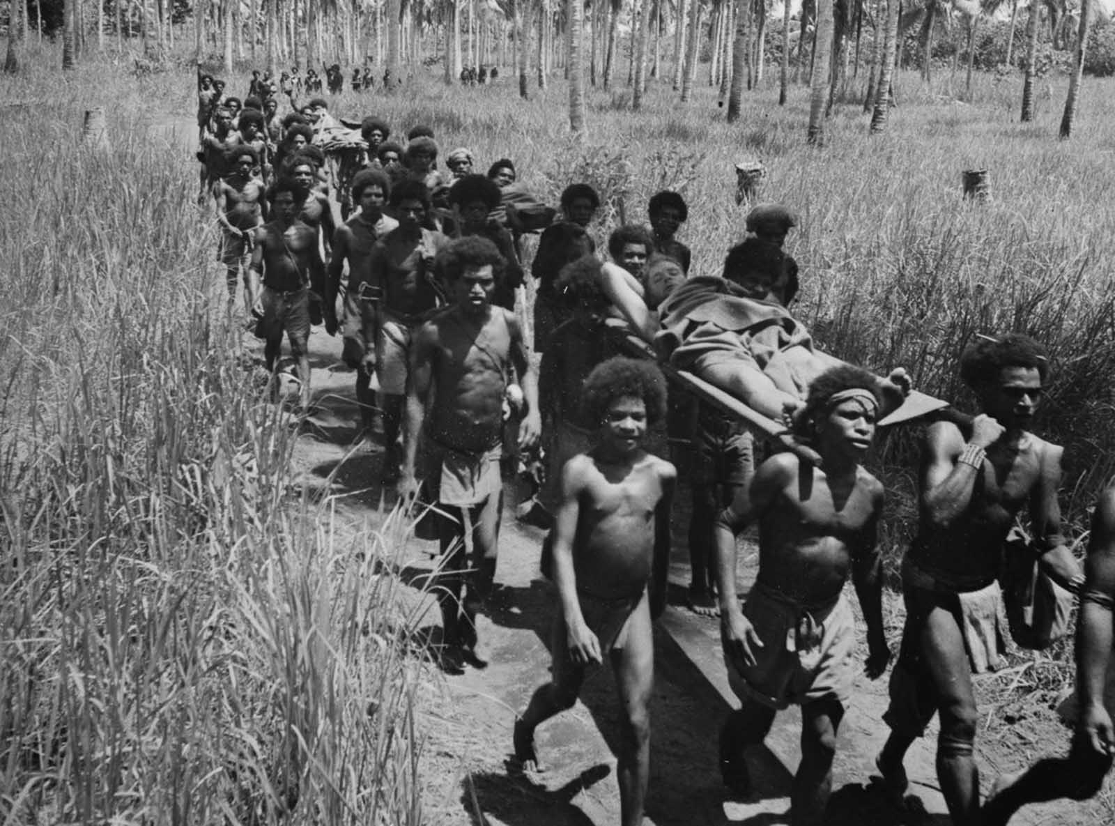Stretcher bearers carry wounded soldiers to a dressing station near Buna.