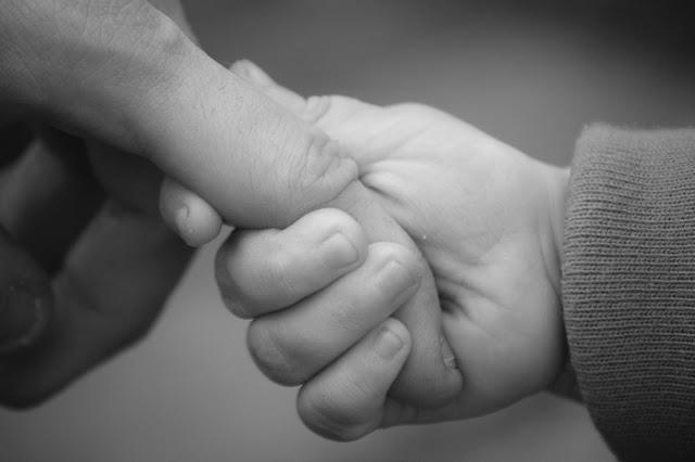 Bébé qui tient la main de son papa